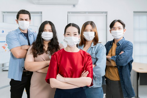 Happy employees in office wearing mask